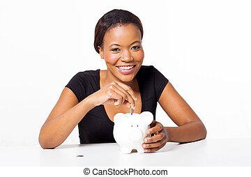 african woman putting coin in piggy bank