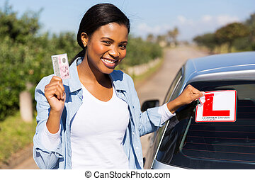 african woman removing learner driver sign after getting her...