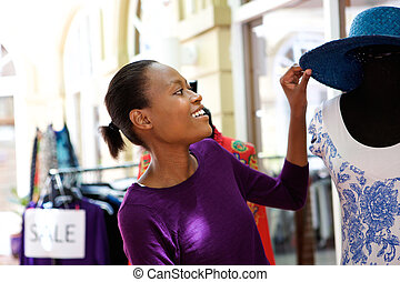 African woman shopping for a hat