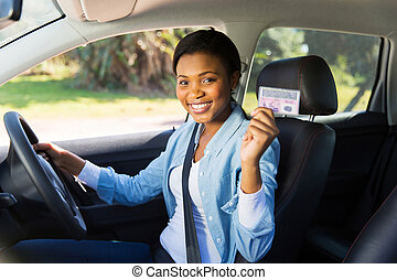 african woman showing her driver's license - pretty african...