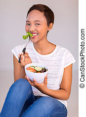 african woman sitting on floor and eating salad