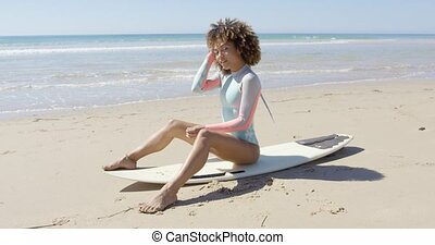 African woman sitting on surfboard - Smiling female sitting...