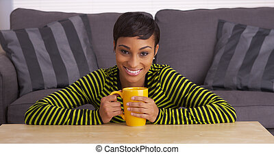 African woman smiling at coffee table with mug