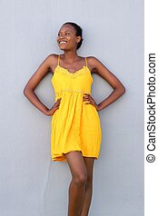 African woman smiling in elegant yellow dress