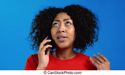 African woman speaking on mobile phone. Mixed race lady holding and using smartphone. Blue studio background. High quality 4k footage