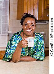 tea break - african woman taking a tea break in the kitchen