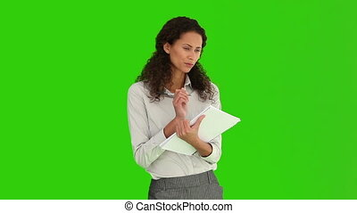 African woman taking note against a green screen