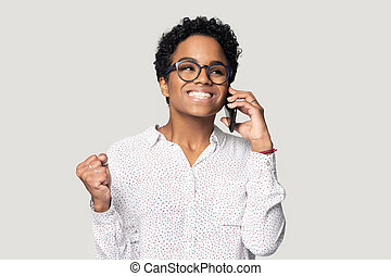 African woman talking on cellphone happy to hear good news
