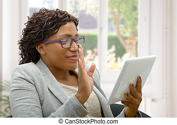 African woman talking online with tablet