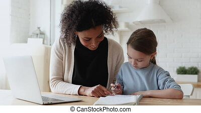 African woman tutor helping caucasian child with homework at...