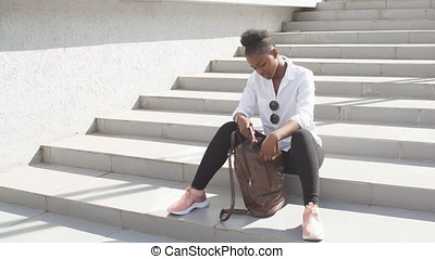 African woman using smart phone while sitting on white...