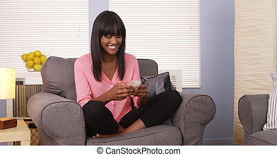 African woman using smartphone on couch
