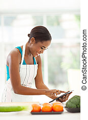 african woman using tablet computer in kitchen