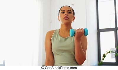 african woman with dumbbells exercising at home