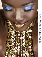 African woman with gold and blue metallic make-up and shiny necklace.