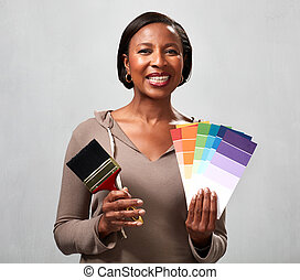 African woman with paintbrush and colors