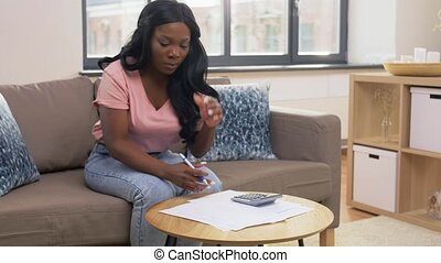accounting, taxes and finances concept - young african american woman in glasses with papers and calculator at home