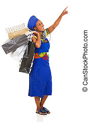 african woman with shopping bags pointing empty space