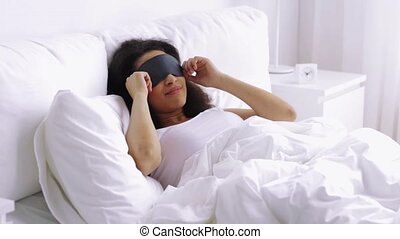 african woman with sleeping mask in bed at home