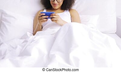 african woman with smartphone in bed at home