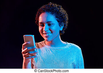 african woman with smartphone in neon lights