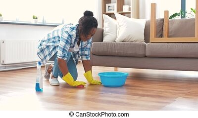 african woman with sponge cleaning floor at home