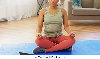 african woman with tablet pc meditating at tome - ...