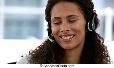 African woman working in call centre with earpiece on
