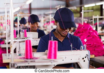 african worker sewing in clothing factory - smiling african...