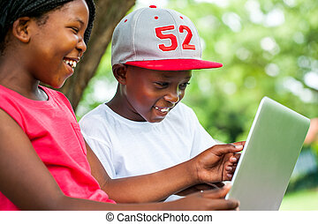 Close up portrait of African youngsters enjoying time with laptop in park.