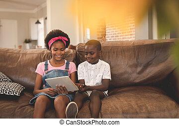 africano, digital, irmão, usando, sofá, americano, tabuleta, sentando