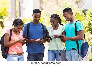 africano, estudante universitário, usando, seu, telefones celulares