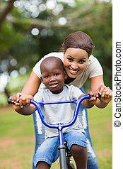 africano, madre, enseñanza, ella, poco, hijo, para montar, un, bicicleta