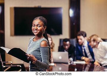 afrikanisch, geschäftsfrau, schauen kamera, in, sitzungssaal, mit, kollegen, in, hintergrund