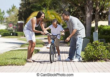 afrikanische amerikanische familie, mit, junge reitfahrrad, &, glücklich, eltern