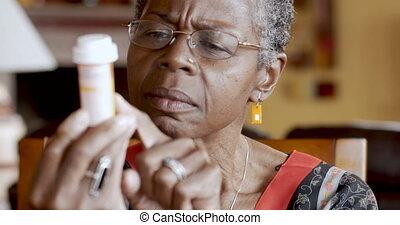afrikanischer amerikaner, ältere frau, schwierig, lesen, a, pillenflasche, etikett, in, sie, hand
