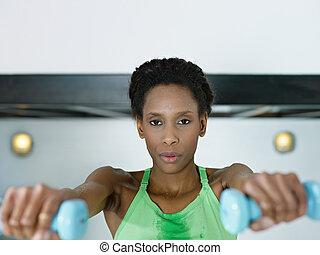 afrikansk kvinna, exercerande, med, liten, vikter, in, gymnastiksal