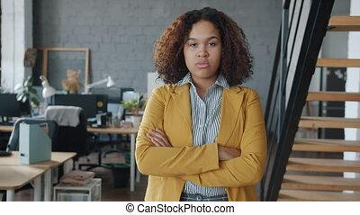 afro-américain, bureau, portrait, femme affaires, ambitieux, debout, armes traversés