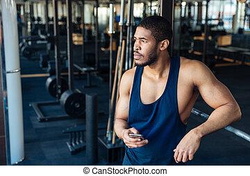 Afro american bodybuilder guy holding smartphone