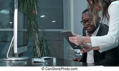 Afro-american boss and his asian secretary using digital tablet