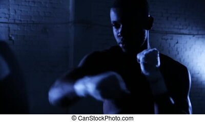 Afro-american boxer athlete shadow boxing in gym