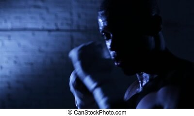 Afro-american boxer athlete shadow boxing in gym. Closeup