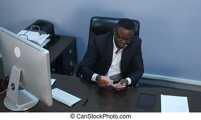 Afro-american businessman counts money, sitting in office