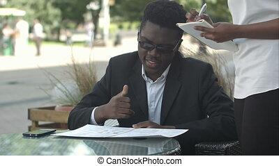 Afro american businessman during work break take an order in...