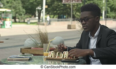 Afro-american businessman eating meal during lunch time in cafe