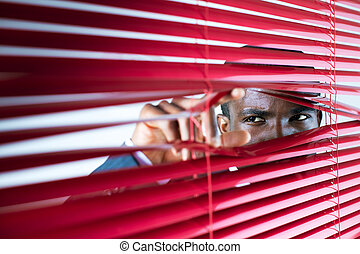 red blinds - afro-american businessman glancing through red ...
