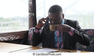 Afro american businessman is calling on smartphone and...