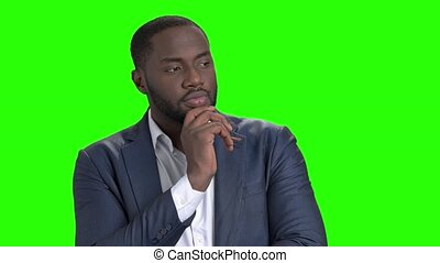 Afro-american businessman is thinking on green screen.