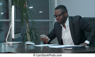 Afro-american businessman reading emails on his smartphone and texting answers