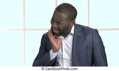 Afro-American businessman suffering from toothache....